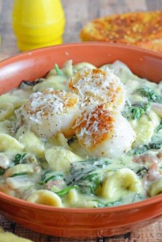 Scallion Pesto Scallop Pasta is a restaurant quality dish, creamy pasta sauce with garlic, Swiss chard, prosciutto and seared scallops. #pastarecipes #scalloprecipes www.savoryexperiments.com