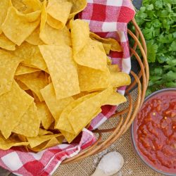 Homemade Tortilla Chips in a basket with salsa and cilantro