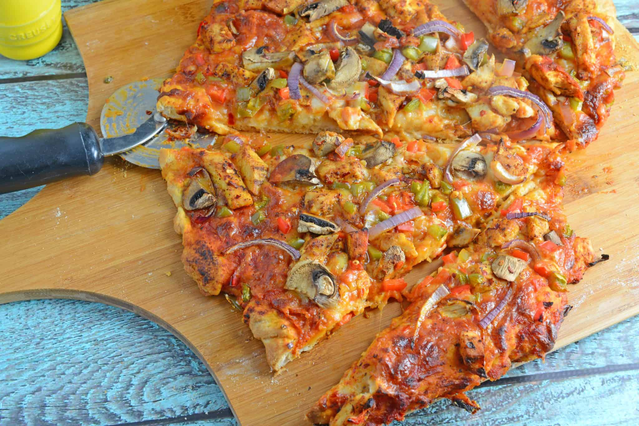 Caribbean Jerk Chicken Pizza is an easy homemade pizza recipe using spicy chicken, fresh vegetables and a touch of honey. #homemadepizza #jerkchicken #jerkchickenpizza www.savoryexperiments.com