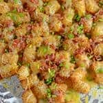 Cheesy Loaded Tater Tots are an easy side dish recipe or appetizer. Loaded tater tots are the best since they are loaded with cheese and bacon! #cheesytatertots #loadedtatertots #appetizerrecipes www.savoryexperiments.com