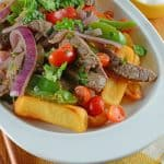Lomo Saltado is a Peruvian dish using tender steak, onions, tomatoes, bell peppers and jalapenos over crispy French fries.