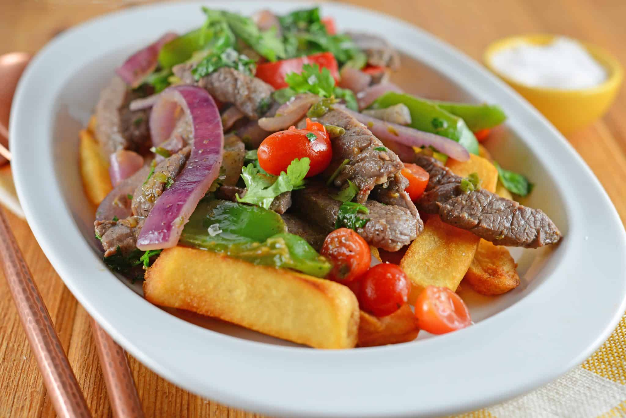 Lomo Saltado is a Peruvian dish using tender steak, onions, tomatoes, bell peppers and jalapenos over crispy French fries. #lomosaltado #steakandpotatoes www.savoryexperiments.com
