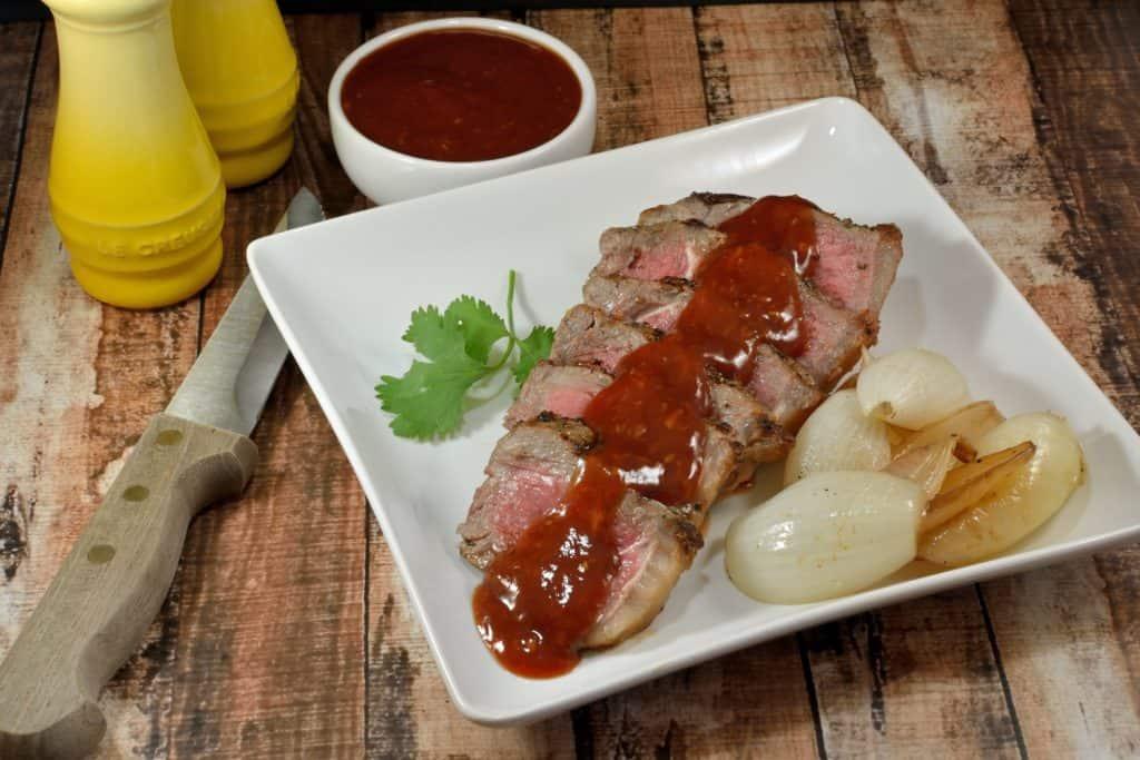 Steak sauce over a sliced piece of beef