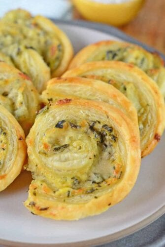 Spinach and Artichoke Pinwheels are an easy party appetizer that everyone will love. Creamy dip rolled in buttery pastry and baked until crispy.