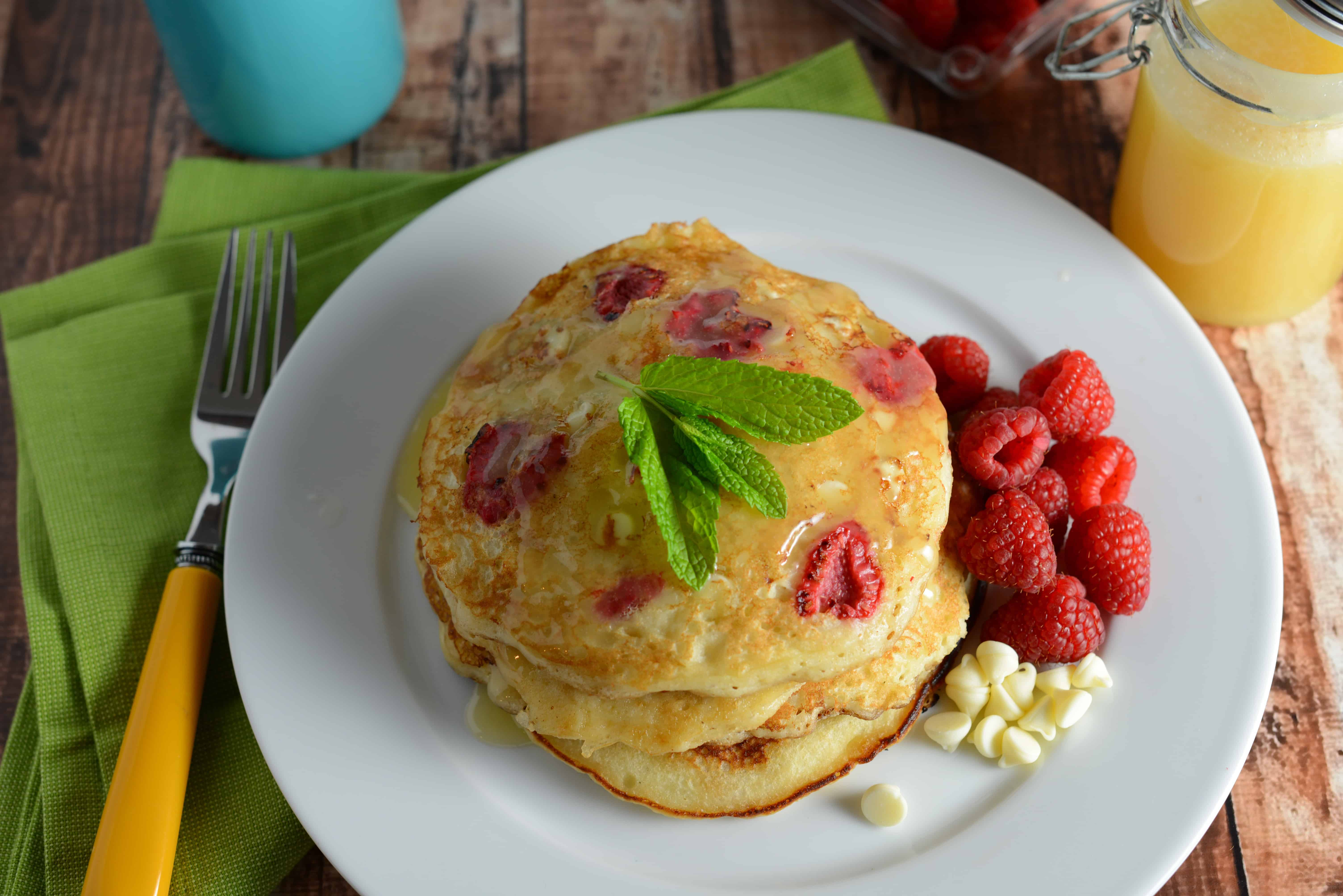 White Chocolate and Raspberry Pancakes Recipe - The perfect fluffy buttermilk pancakes dotted with fresh raspberries, white chocolate chips and homemade Dutch honey syrup. www.savoryexperiments.com