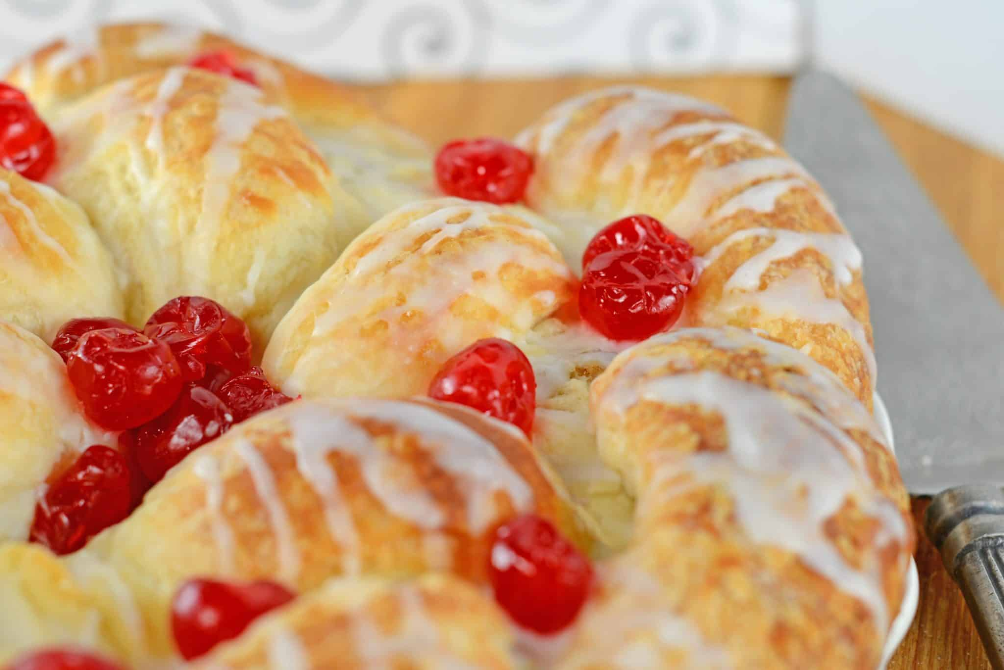 Danish Pastry Wreath is a buttery, flakey pastry stuffed with almond filling and gently glazed with a powdered sugar frosting and candied cherries.