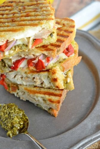 Italian Chicken Panini Recipe - Crusty bread filled with gooey mozzarella cheese, roasted red pepper, shredded chicken and lots and lots of garlicky pesto. www.savoryexperiments.com