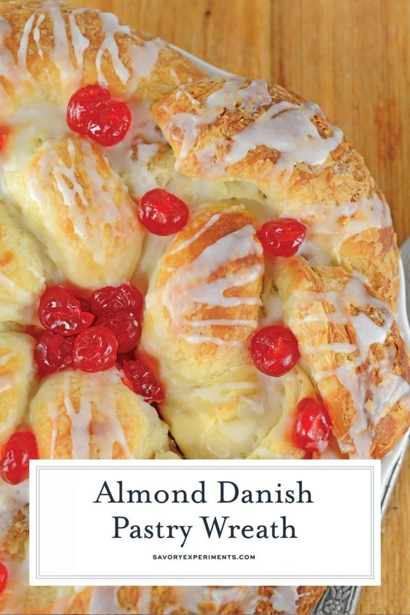 Almond Danish Pastry Wreath is a buttery, flakey pastry stuffed with almond filling and gently glazed with a powdered sugar frosting and candied cherries. #danishpastry #pastrywreath #howtomakepastry www.savoryexperiments.com