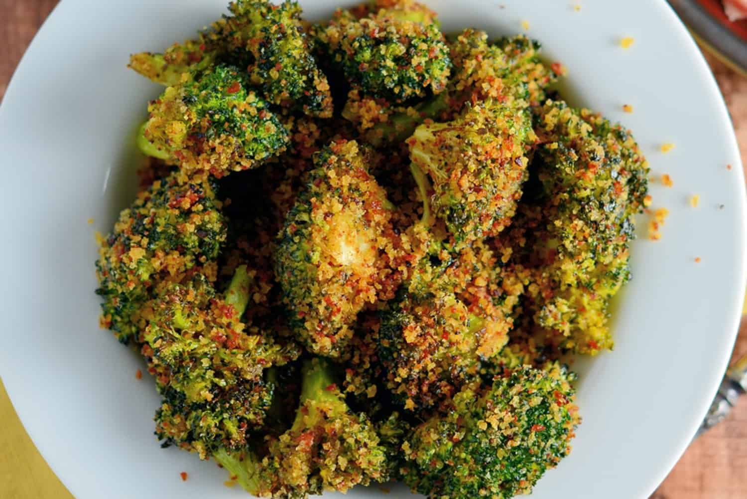 Crunchy baked broccoli tossed in a crisp, tangy mix with two secret ingredients that will make this broccoli recipe your favorite side dish!   #bakedbroccoli #ovenbakedbroccoli www.savoryexperiments.com