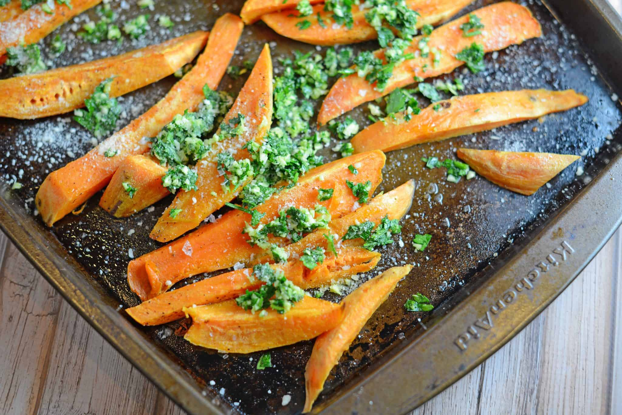 Garlic Parmesan Baked Sweet Potato Fries will jazz up your dinner with lightly tossed herbs, cheese and tender sweet potatoes! #sweetpotatofries #bakedsweetpotatofries #sweetpotatorecipes www.savoryexperiments.com