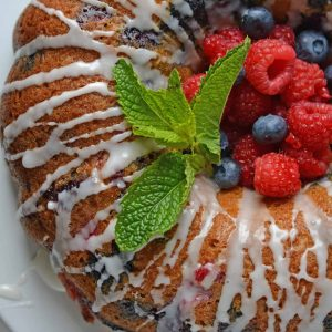 berry buttermilk bundt cake with glaze and fresh mint