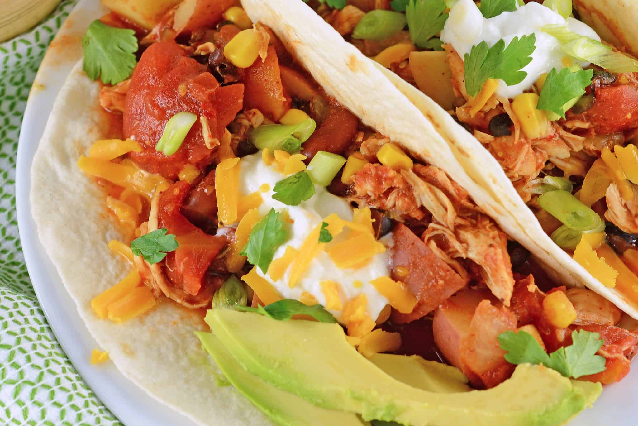 Slow Cooker Cowboy Chicken is an easy chicken recipe your whole family will love, packed with corn, potatoes, bean and a zesty taco seasoning! #slowcookerrecipes #easychickenrecipes www.savoryexperiments.com