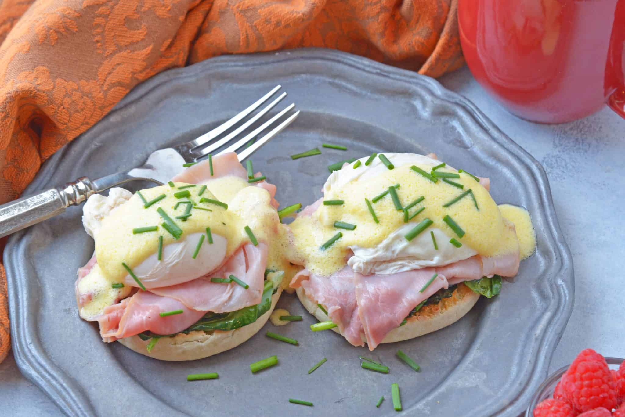 Simple Eggs Benedict tops toasted English muffins with wilted spinach, Canadian bacon, perfectly poached eggs and easy hollandaise sauce. #eggsbenedictrecipe #easyeggsbenedict www.savoryexperiments.com