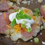 Loaded Smashed Potatoes are a cross between a loaded baked potato and loaded mashed potatoes. Topped with a zesty butter sauce, cheese, bacon, sour cream and scallions. #smashedpotatoes #potatorecipes www.savoryexperiments.com
