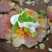 Loaded Smashed Potatoes are a cross between a loaded baked potato and loaded mashed potatoes. Topped with a zesty butter sauce, cheese, bacon, sour cream and scallions.#smashedpotatoes #potatorecipes www.savoryexperiments.com