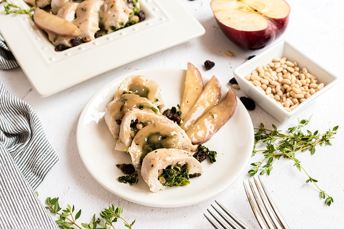 spinach stuffed chicken with apple gravy on a white plate