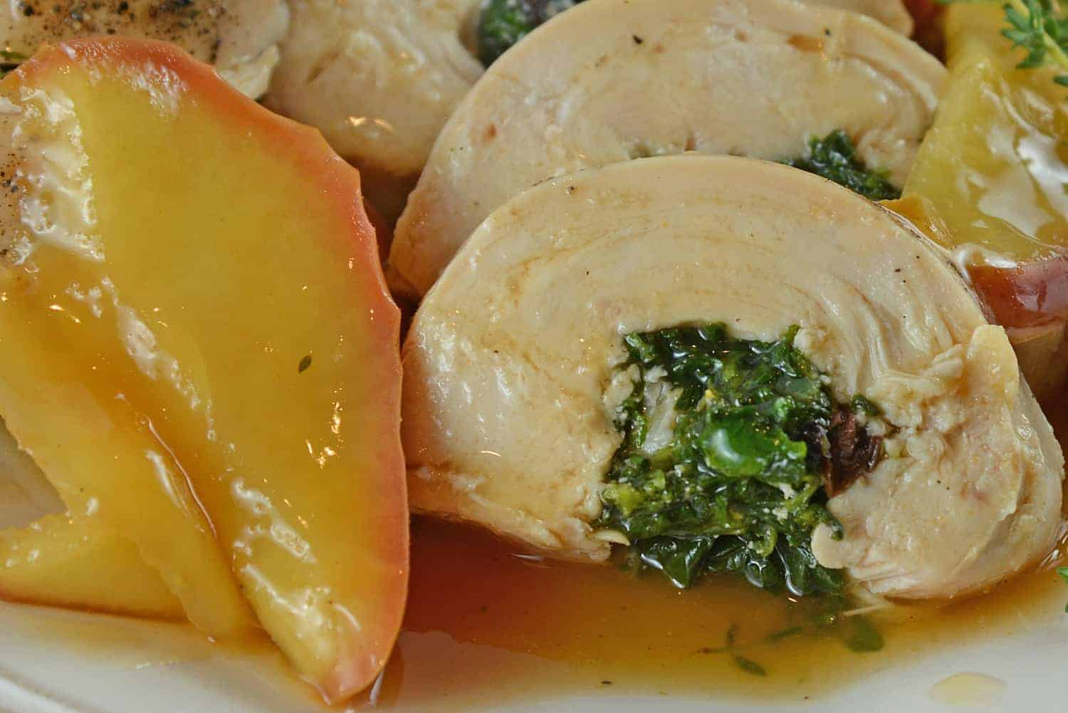 Award winning Stuffed Chicken with Apple Gravy uses pine nuts, spinach, currants and garlic with a savory apple gravy finishes off this easy dinner recipe! #stuffedchicken #easychickenrecipes www.savoryexperiments.com
