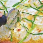 pizza cutter slicing veggie pizza