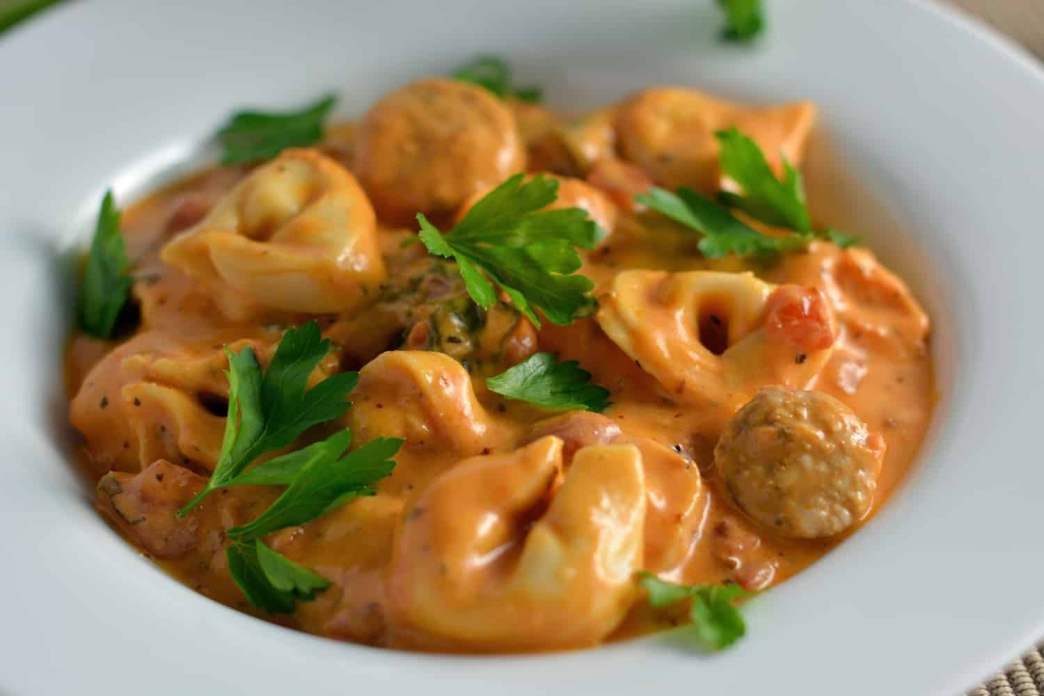 Creamy Tortellini and Sausage Soup can be made in the slow cooker, instant pot or on the stove top. Cheesy tortellini with zesty sauce in a tomato based soup! #sausagesoup #tortellinisoup #slowcookersoup www.savoryexperiments.com