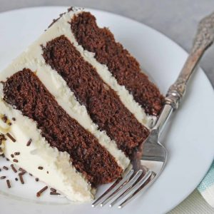 Slice of three layer chocolate cake on a white plate with fork