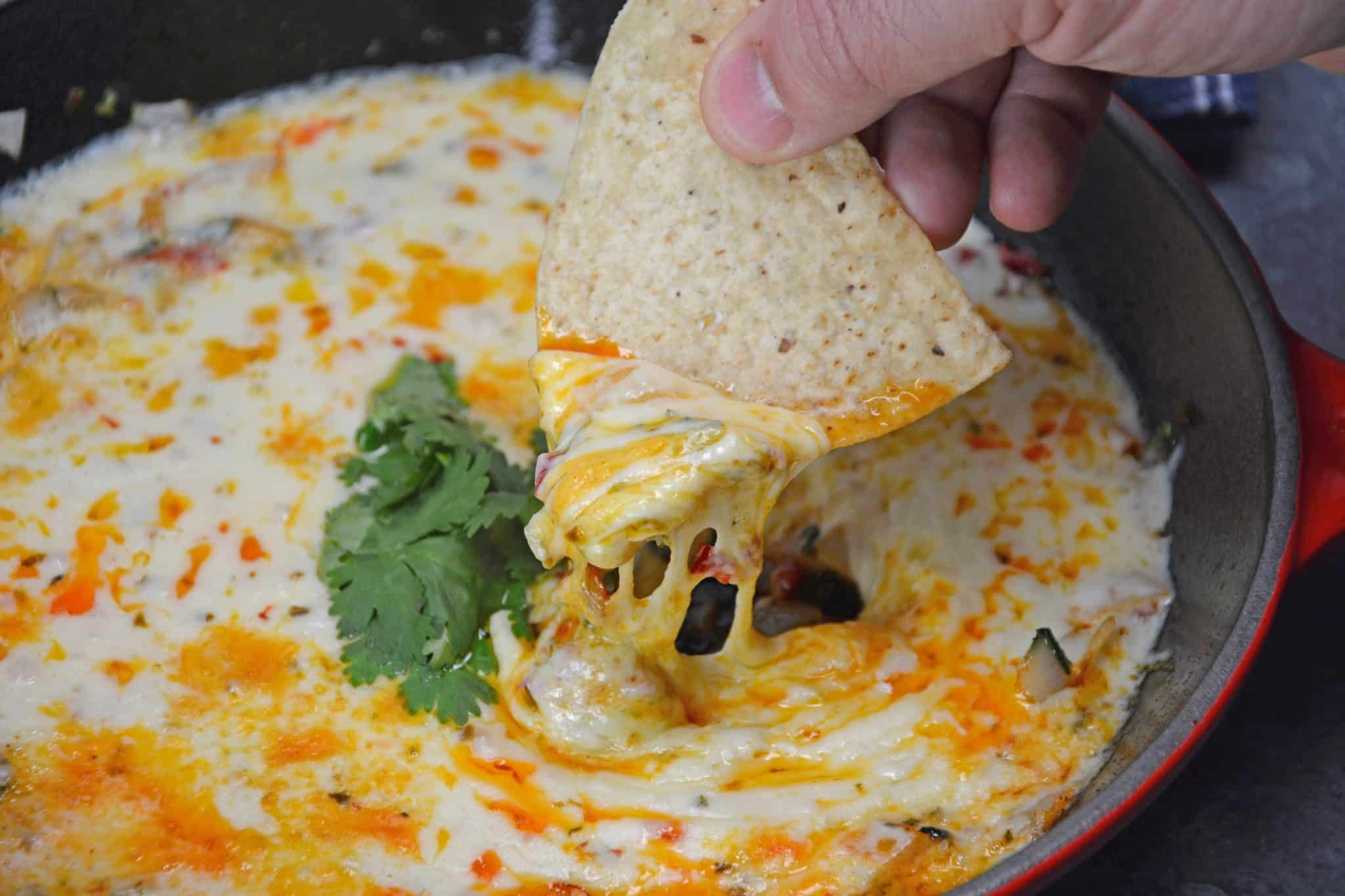 Queso Fundido is an easy Mexican appetizer made of chopped vegetables, cilantro, chile powder and shredded cheddar and pepper jack cheese.