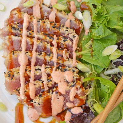 Teriyaki Ahi Tuna on a white plate with leafy greens