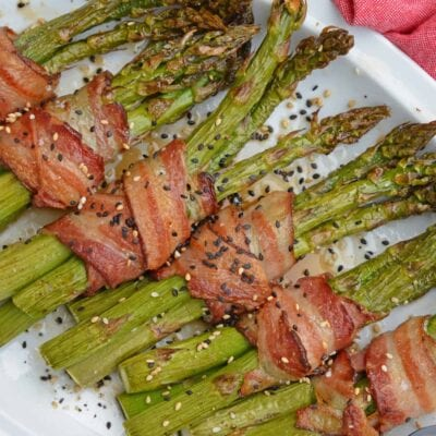 Bacon Wrapped Asparagus with apricot preserves is a mouthwatering side dish that belongs next to anything grilled. This side dish only takes 20 minutes to cook! #baconwrappedasparagus #bakedasparagus www.savoryexperiments.com