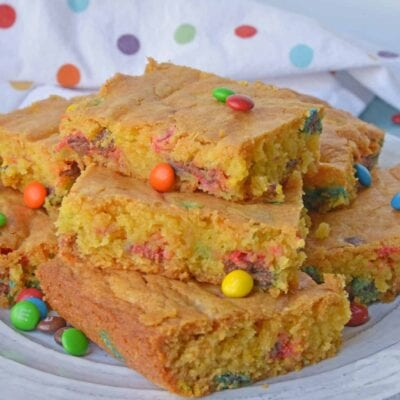 Thick and chewy M&M Cookie Bars are perfect for your cookie exchange, dessert potluck or an after school snack using just a few ingredients!#cookiebars #easydessertrecipes www.savoryexperiments.com
