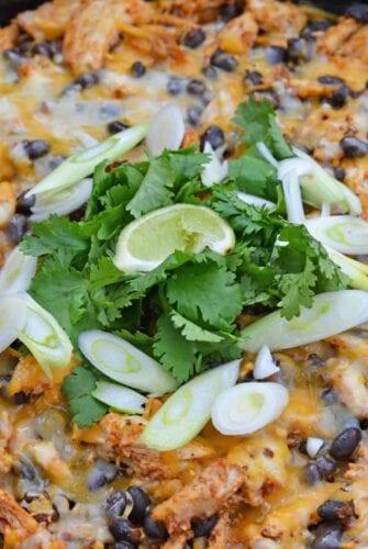chicken enchilada casserole in cast iron with scallions