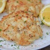Close up of Maryland Crab Cakes on a white plate with lemons