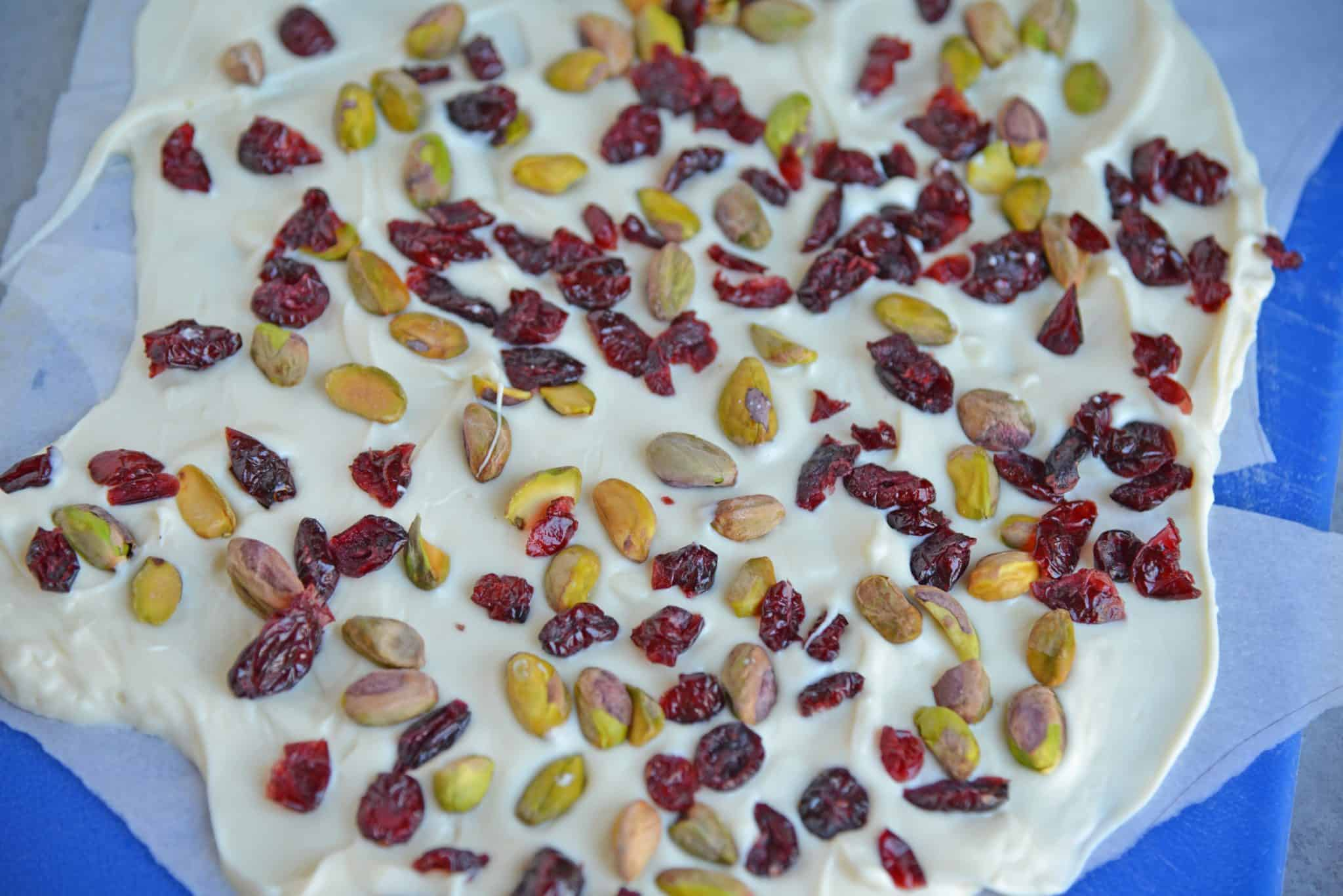 Pistachio Cranberry Bark is a delicious combination of pistachios, cranberries, and white chocolate! Perfect for the holiday season with its festive colors! #christmasbarkrecipe #pistachiocranberrybark www.savoryexperiments.com
