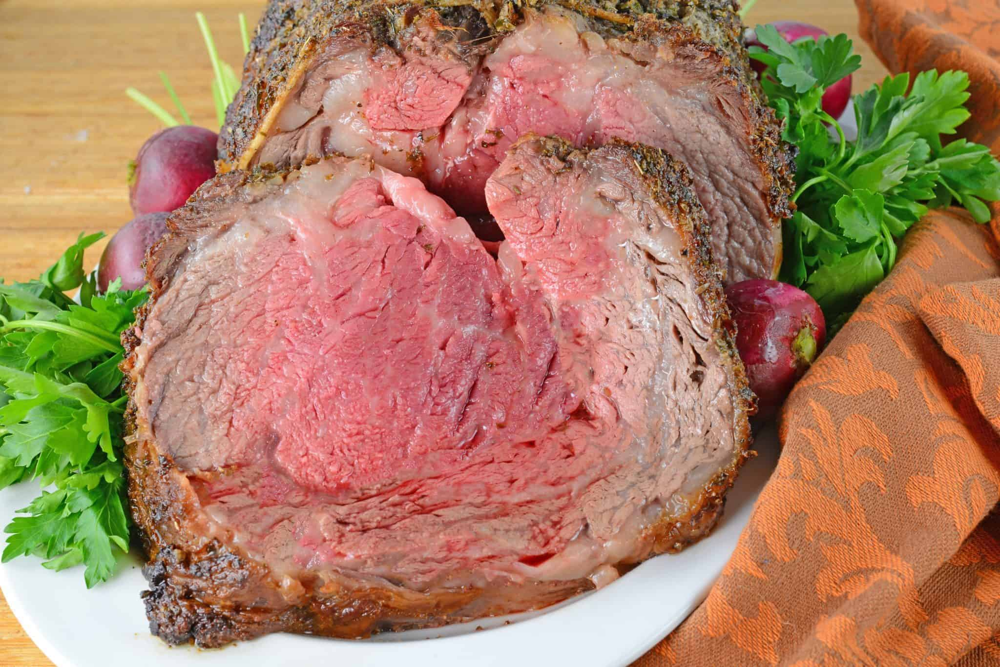 Prime Rib, or rib roast, is studded with garlic and rubbed with spice mix to create a flavorful bark. Easy step-by-step instructions for perfect prime rib!
