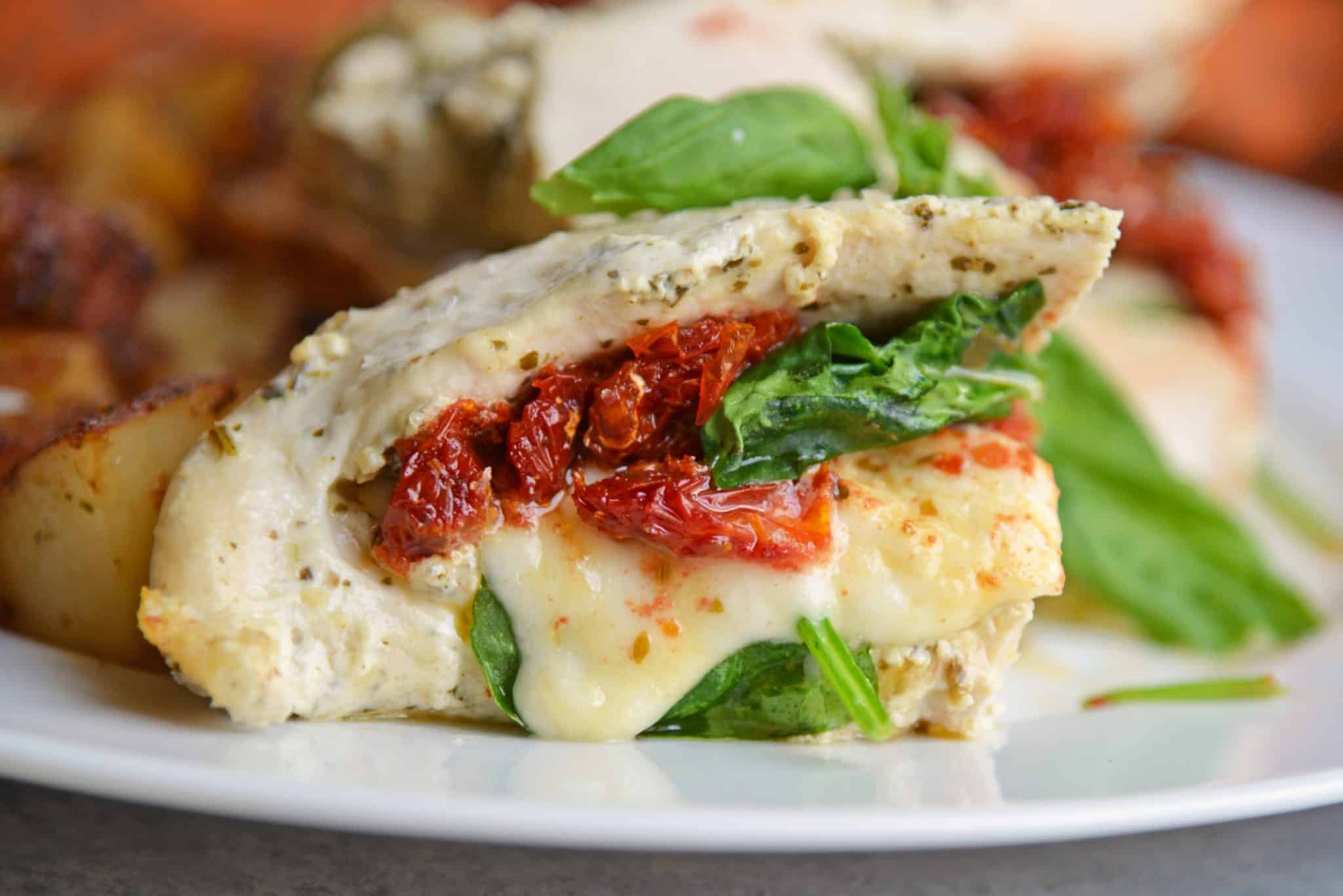 Pesto Spinach Stuffed Chicken are chicken breasts stuffed with gooey mozzarella cheese, sun dried tomatoes and spinach. Marinated in a yogurt and basil pesto sauce, they are moist and flavorful. #stuffedchicken #spinachstuffedchicken www.savoryexperiments.com
