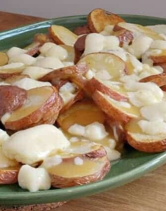 This Poutine Recipe is a delicious, classic Canadian dish made from French fries, cheese curds and gravy! Poutine is pure mouth watering comfort food! #poutinerecipe #whatispoutine #canadianpoutine www.savoryexperiments.com