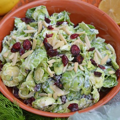 Cranberry Almond Brussel Sprout Slaw is a healthy and delicious way to eat raw brussels sprouts. Mixed with yogurt, dill, cranberry and almond, it is packed with flavor! #brusselsproutsrecipe #brusselsproutsalad www.savoryexperiments.com
