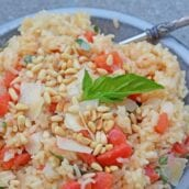 Tomato Parmesan Risotto is a creamy and delicious Italian style risotto recipe. Made with tomatoes, basil, garlic, pine nuts, and parmesan cheese! #risottorecipe #howtocookrisotto #parmesanrisotto www.savoryexperiments.com