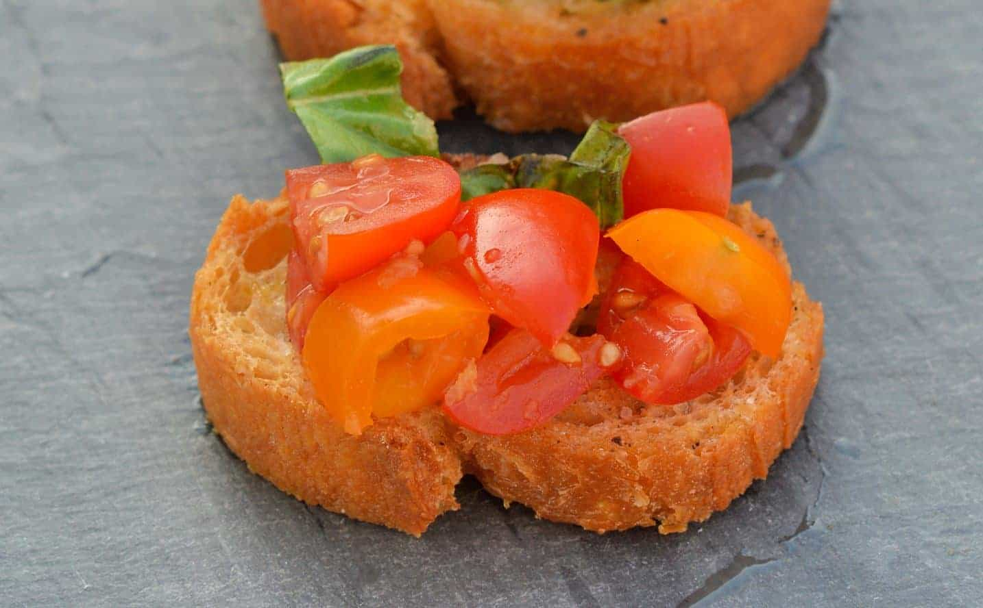 This Tomato Bruschetta recipe is a classic no cook appetizer that can be ready in as little as 20 minutes using fresh tomatoes, basil and garlic. #easybruschetta #tomatobruschetta www.savoryexperiments.com