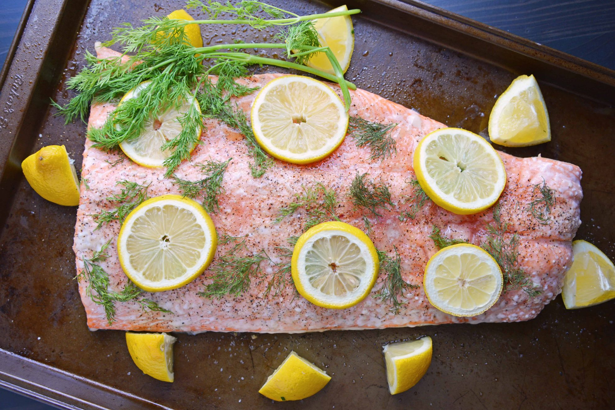 Overhead of whole salmon fillet with lemons and dill