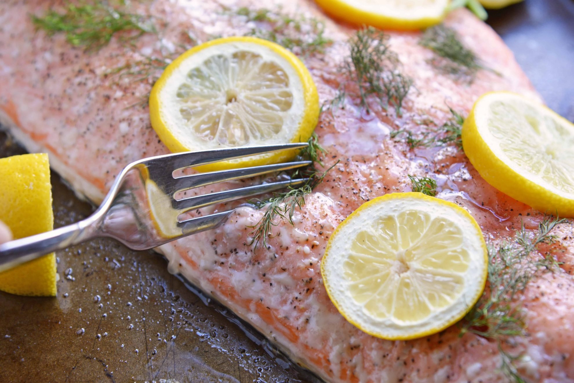 Fork cutting into salmon fillet with lemon slices