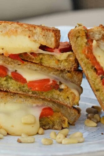 Pesto Grilled Cheese is a gooey grilled cheese recipe featuring Jarlsberg cheese, roasted red peppers, pesto, and pine nuts and sourdough bread! #pestogrilledcheese #grilledcheeserecipe www.savoryexperiments.com