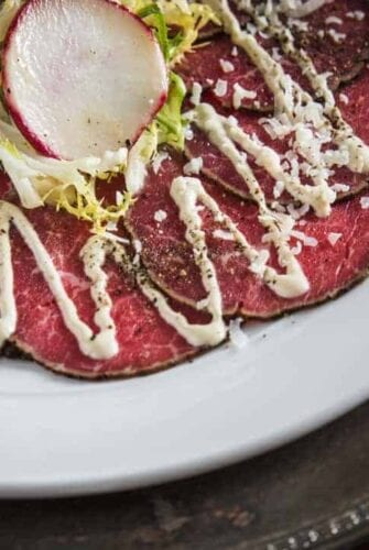 Close up of Beef Tenderloin Carpaccio salad topped with dijon lime dressing