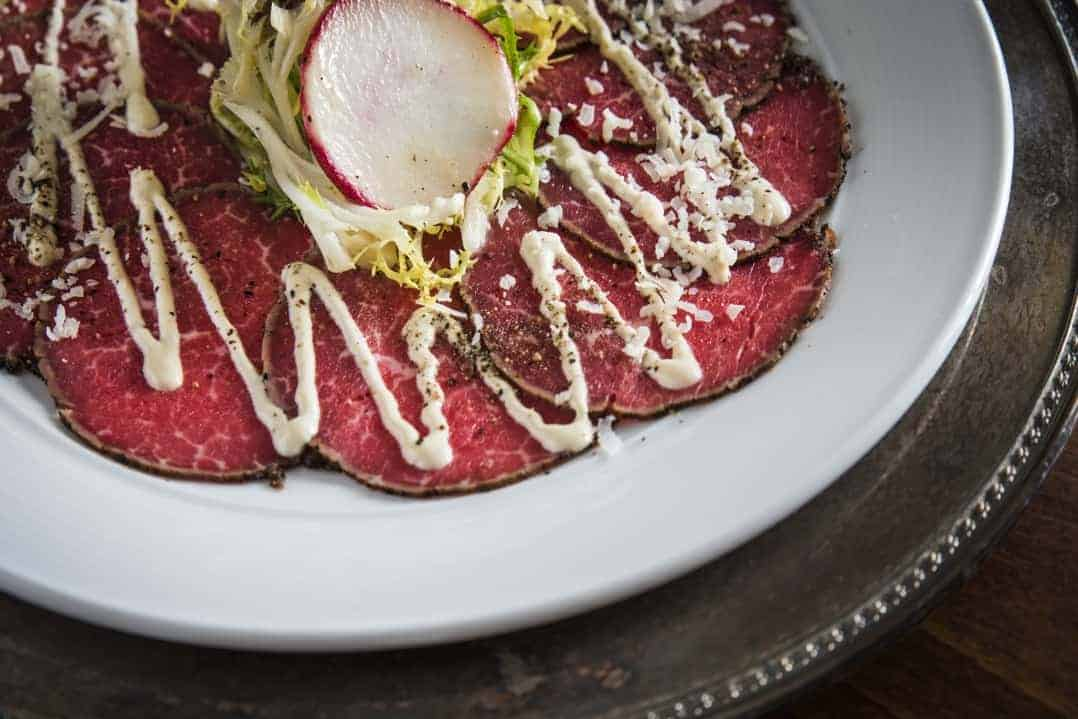 Learn how to make this Beef Tenderloin Carpaccio at home with a tangy side sauce! It's a simple and elegant dish that can be added to salads or other appetizers! #beefcarpacio www.savoryexperiments.com