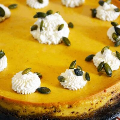 This easy Pumpkin Cheesecake recipe features a gingersnap crust topped, salty pumpkin seeds, and pumpkin spiced whipped cream. Simple and delicious! #pumpkincheescake #cheesecake #gingersnaps www.savoryexperiments.com