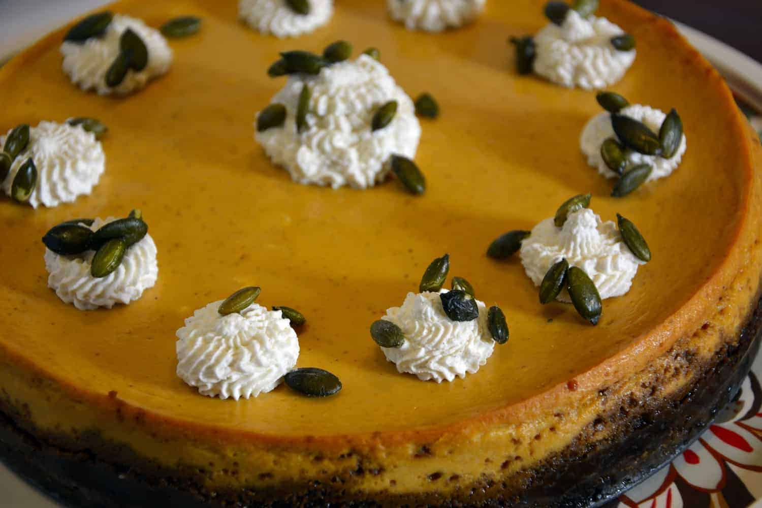 Pumpkin Cheesecake with Spiced Whipped Cream and Salted Pumpkin Seeds- complex flavors and textures, but simple to make. #pumkpin #cheesecake #pumpkincheesecake