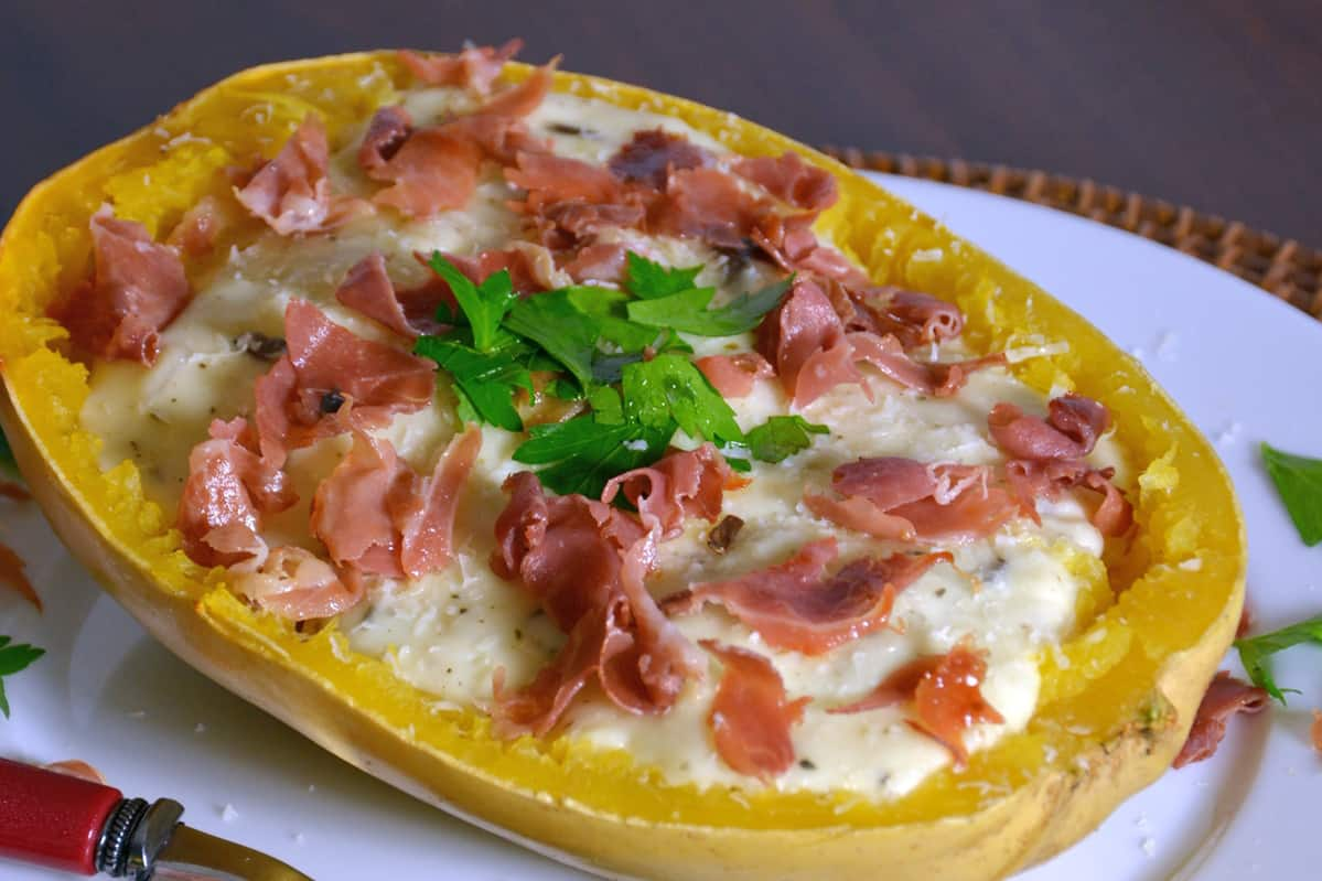 Creamy Brie Spaghetti Squash uses the tender golden strands of baked spaghetti squash and pairs them with a decedent brie sauce, mushrooms and crispy prosciutto.#bakedspaghettisquash #briesauce www.savoryexperiments.com