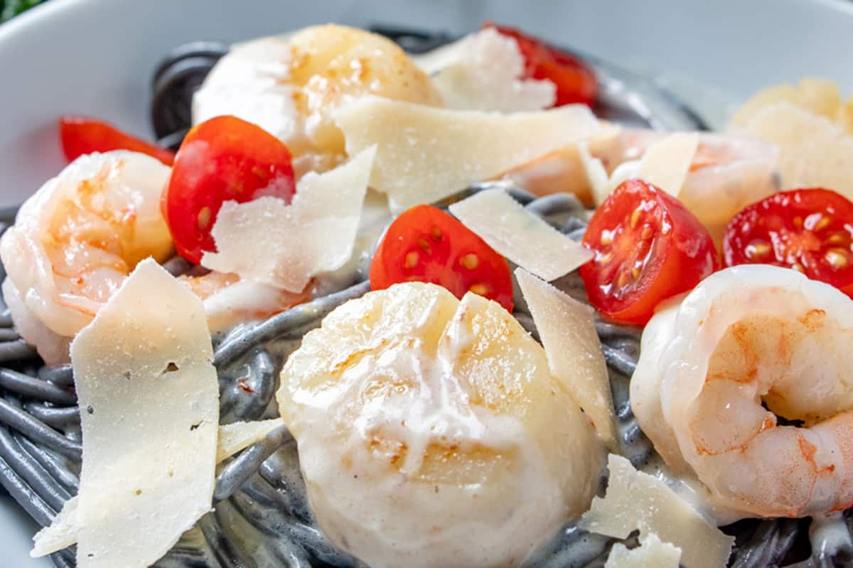 close up of scallop with black pasta