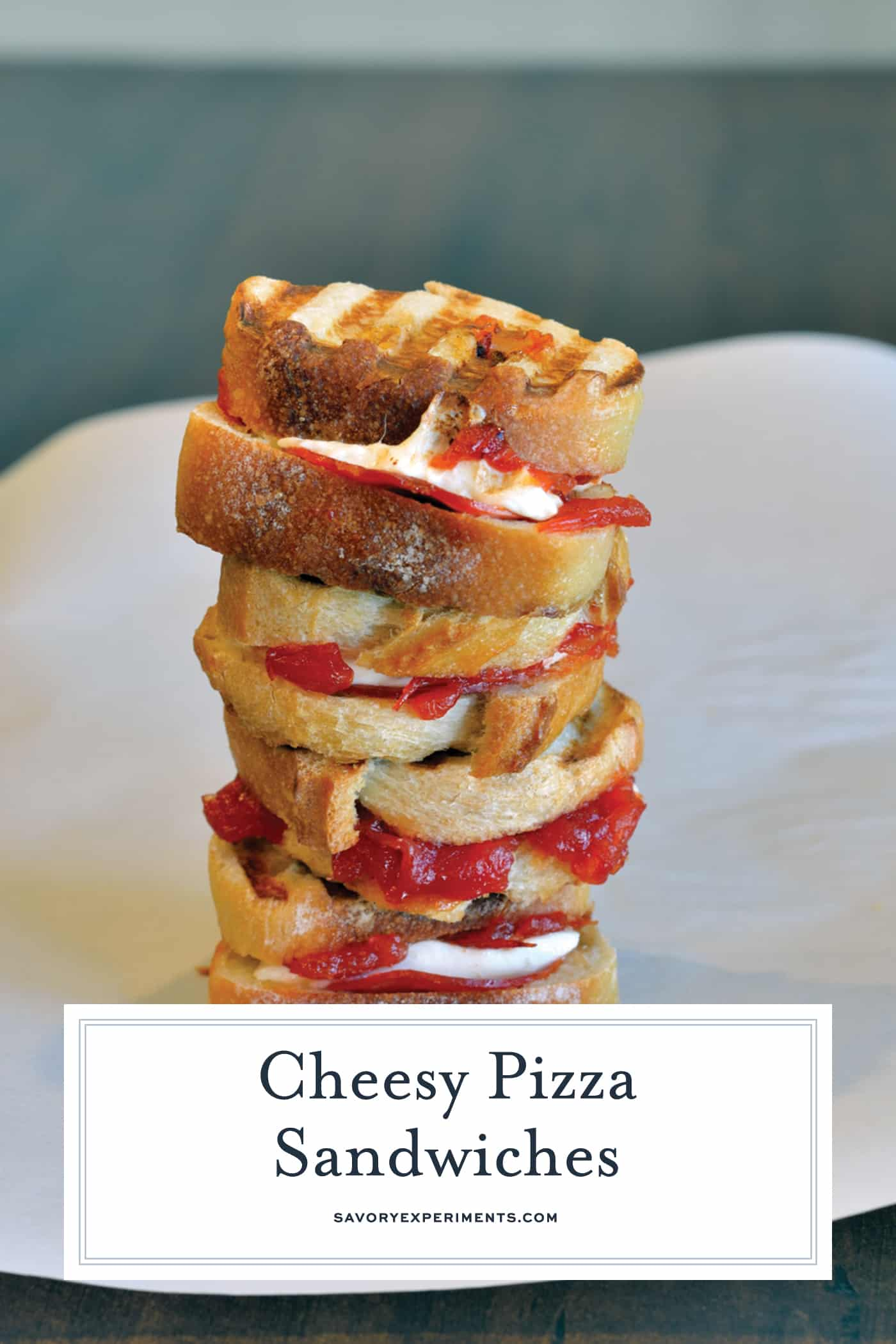 Cheesy Pizza Sandwiches are mini, slider-size grilled cheese sandwiches with mozzarella cheese, tomato jam and pepperoni. Kid friendly and great for parties!#pizzasandwiches www.savoryexperiments.com