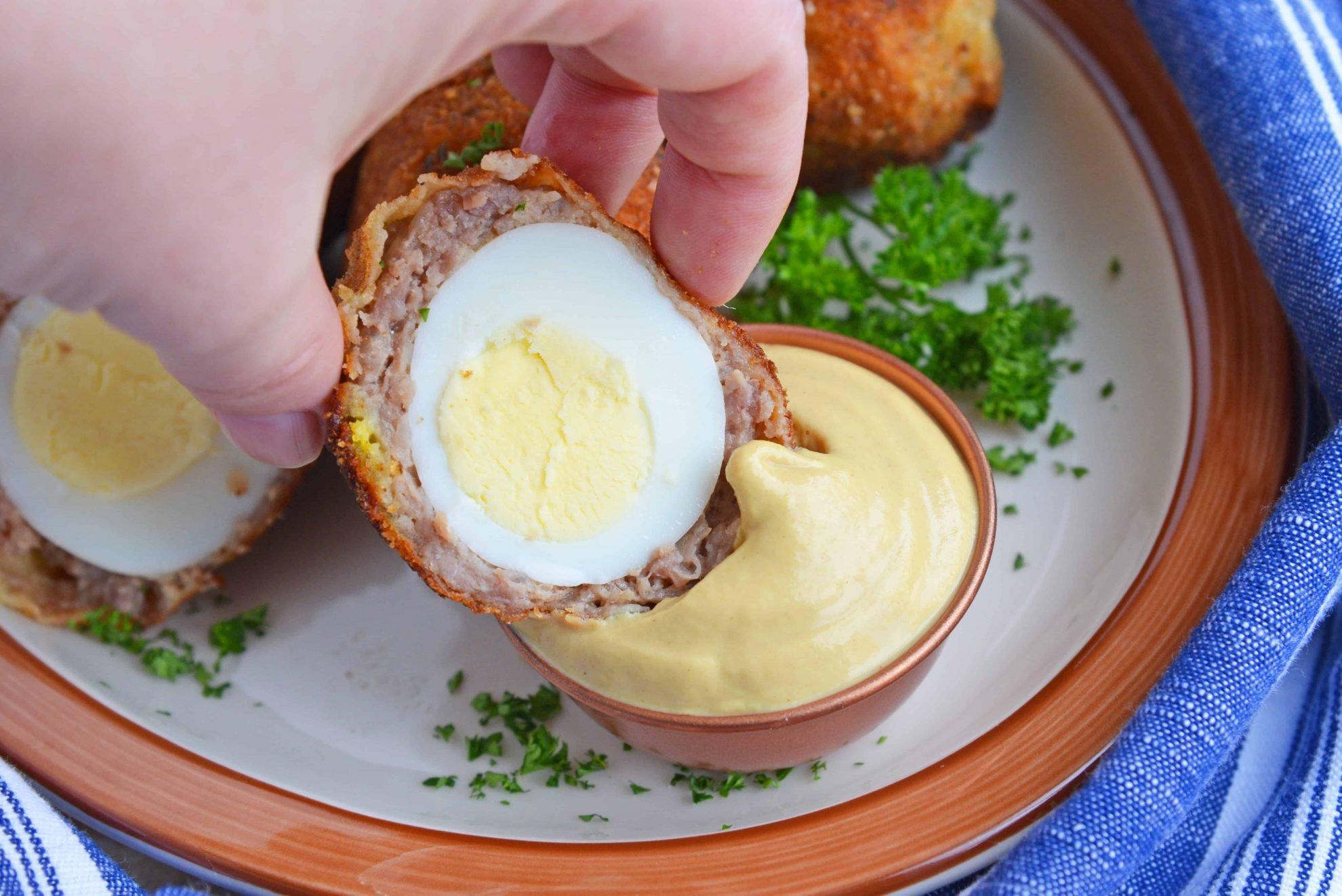 Scotch Egg dipping in Dijon mustard