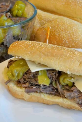 Slow Cooker Italian Beef Hoagies are tender beef with moderately hot pepperoncini chiles, smothered with cheese and loaded onto a hearty roll. | #slowcookermeals | www.savoryexperiments.com