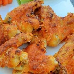"Crispy Baked Buffalo Wings uses a secret ingredient to ""bread"" wings. Bake to crispy perfection and toss in a garlic buffalo sauce.#bakedbuffalowings #crispychickenwings www.savoryexperiments.com"